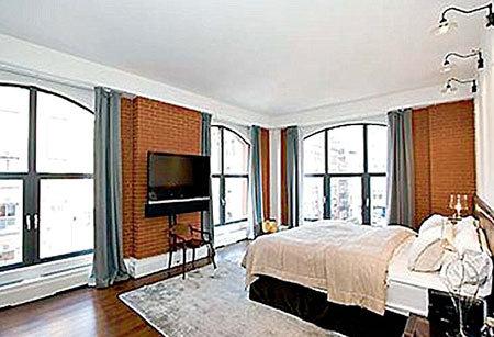 В спальне хозяина лишь кровать да телевизор, зато на окнах плотные шторы