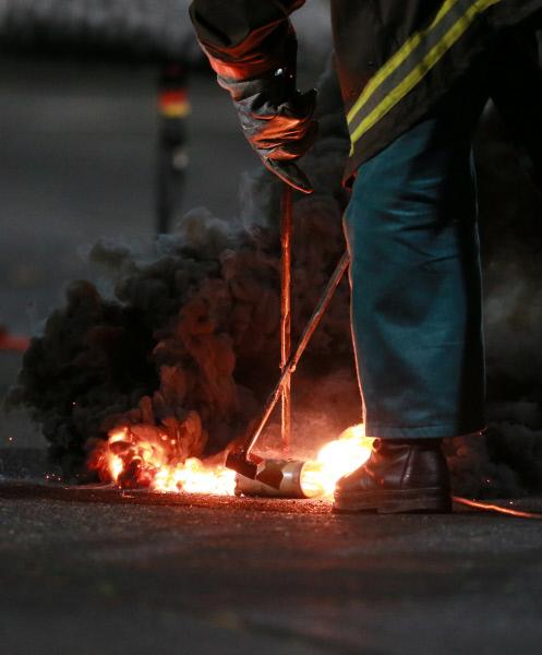 Сотрудник пожарной охраны стадиона тушит файер, брошенный на поле болельщиками