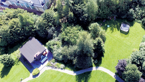 На заднем дворе, в тенёчке, у маленькой Надюши собственная детская площадка с качелями, лесенками и батутом. А неподалеку - беседка со стационарным мангалом. Возле неё теннисный стол. Фото Руслана ВОРОНОГО