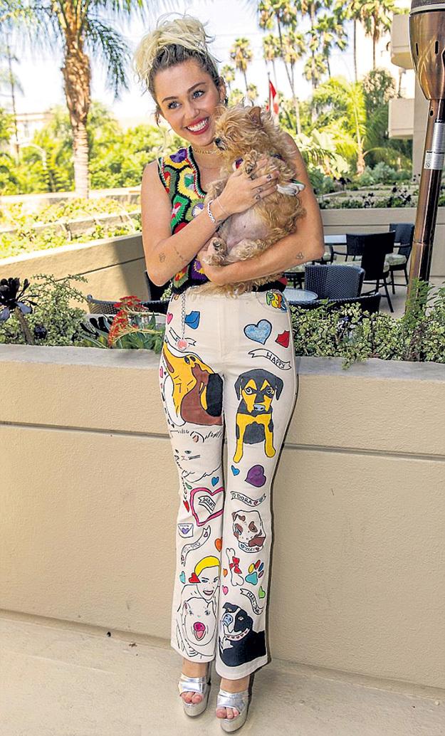 Пресс-конференцию Майли давала в собачьем стиле (Брюки - Prada $1250)